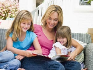 mother and two daughters reading a book