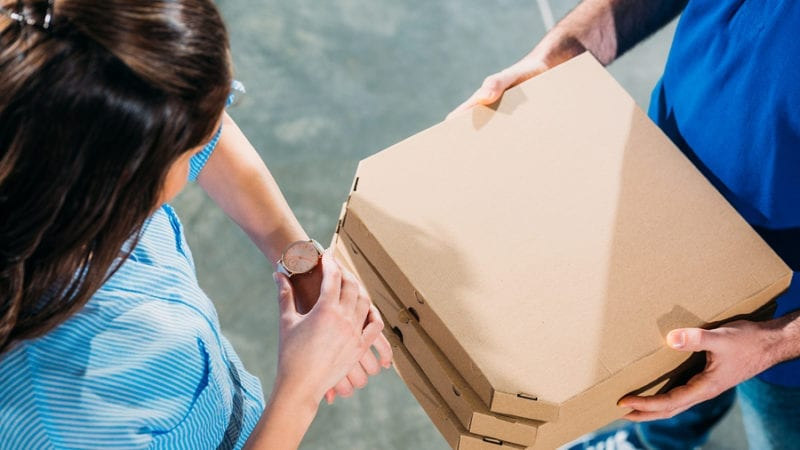 Woman checking her watch when meeting courier with pizzas