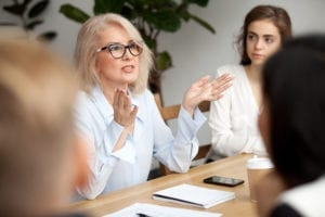 Attractive aged businesswoman, teacher or mentor coach speaking to young people,