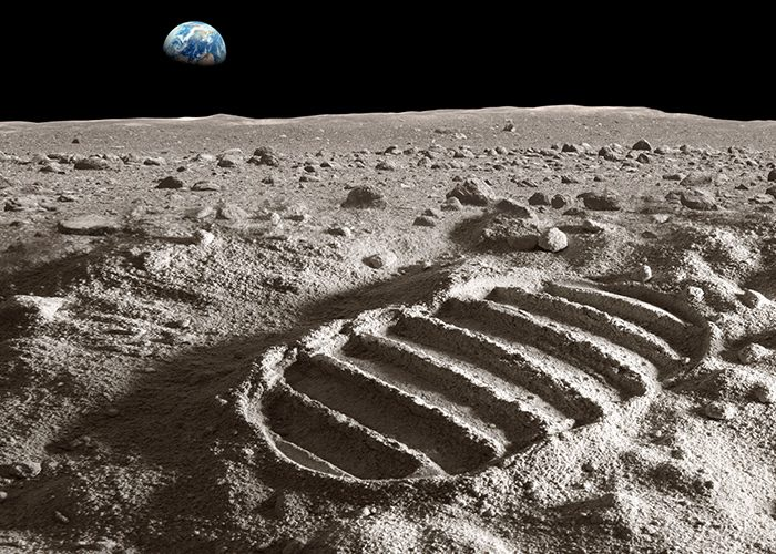Footprint on moon with Earth over the horizon