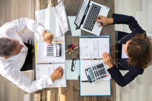 Two accountants using technology across the table from one another