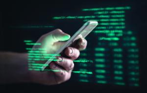 Darkweb, darknet and hacking concept. Hacker with cellphone. Man using dark web with smartphone. Mobile phone fraud, online scam and cyber security threat. Scammer using stolen cell. AR data code.