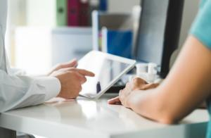 Doctor with tablet and patient having a discussion, meeting and appointment in hospital office room. Physician, surgeon or medic showing medical record or results. Modern technology in health care.