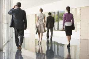 Four lawyers on mobile phones Walking in Office Corridor