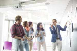 Creative businessman giving presentation to colleagues in office