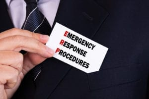 Businessman putting a card with text emergency response procedures in the pocket