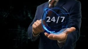 Businessman shows concept hologram 24 7 on his hand. Man in business suit with future technology screen and modern cosmic background