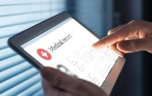 Medical record in electronic form. Digital EMR with patient health care information. Doctor using tablet in hospital or clinic. Personal data in mobile device. Online database for healthcare history.