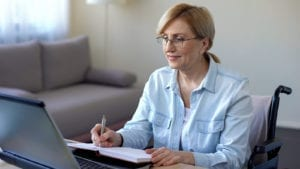 Senior woman in wheelchair studying online and making notes, video lessons