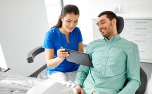 medicine, dentistry and healthcare concept - female dentist with tablet pc computer and male patient discussing teeth treatment at dental clinic office
