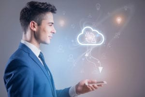 Cloud computing solution ideas. Profile of positive young man is holding smartphone and touching screen of gadget while connecting to cloud storage to synchronize with his contacts