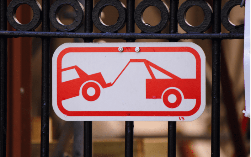 Sign showing a tow truck repossessing a car