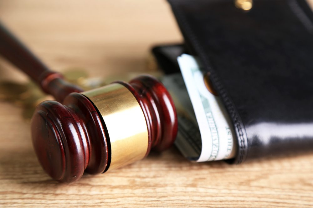 Gavel Next to Money sticking out of leather wallet