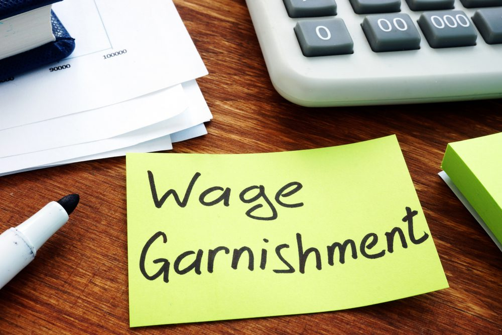 Wage Garnishment on Post-It Note on Desk Near Marker and Calculator