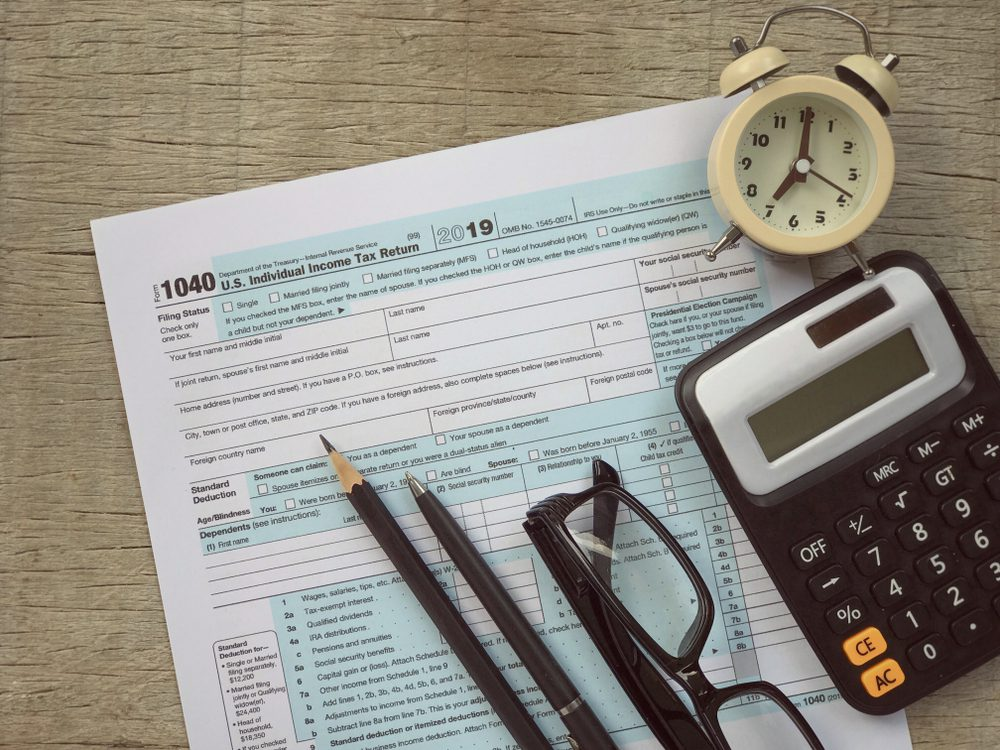 IRS Tax Form With Calculator Clock Glasses and Writing Utensils